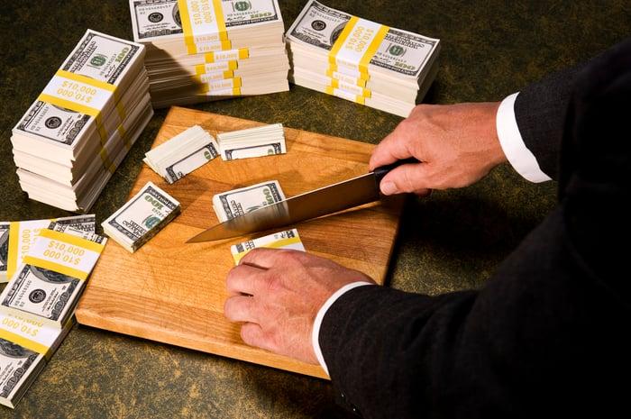 A man cuts stacks of $100 bills on a cutting board.