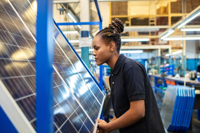 A woman working on a solar panel in a factory.