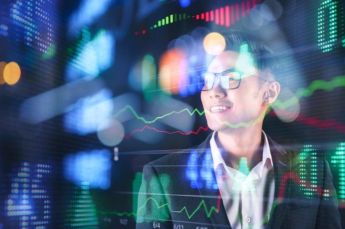 A man smiles while looking at virtual representations of charts and graphs.