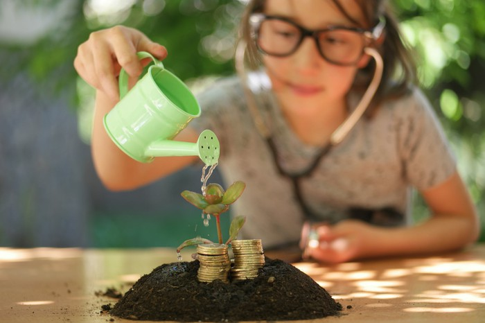 A young person pouring water on a stack of coins on top of soil as if trying to make them grow.