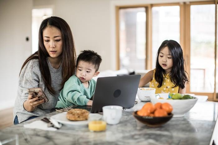 Une famille est assise à la table du petit déjeuner.  La mère regarde son téléphone, tandis que le fils est assis devant un ordinateur portable.
