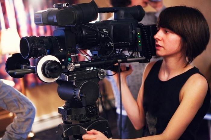 Woman using a camera to film a movie.