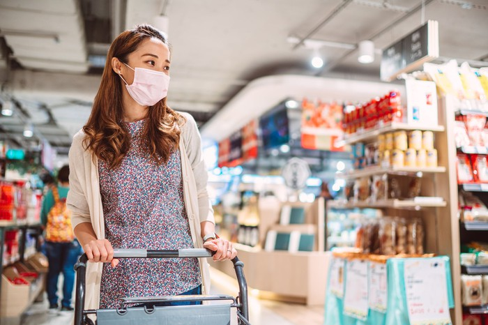 A woman with a mask on shopping in a grocery store.