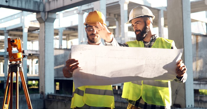 Construction workers looking at a blueprint on a jobsite.
