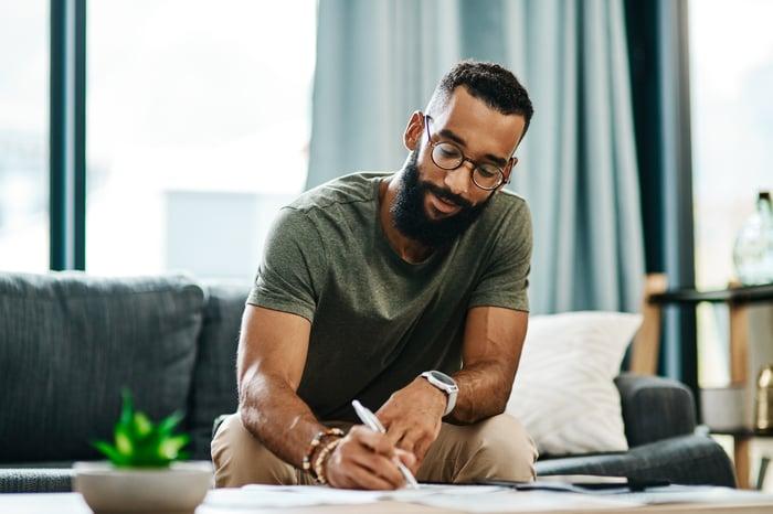 La personne est assise sur un canapé devant une grande fenêtre, écrivant quelque chose sur un morceau de papier.
