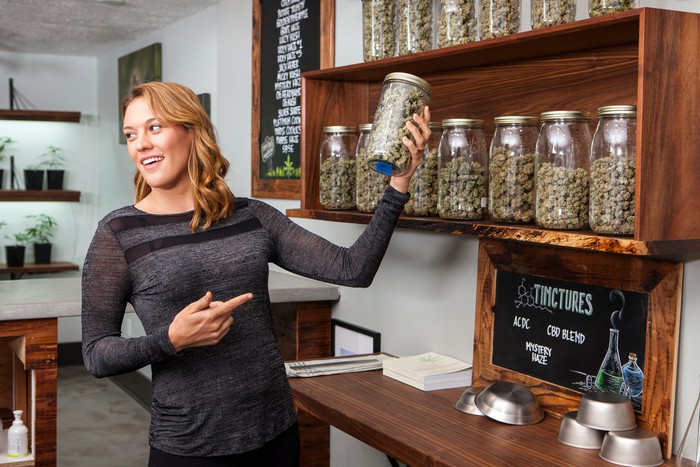 Budtender takes a jar of cannabis off a dispensary shelf.