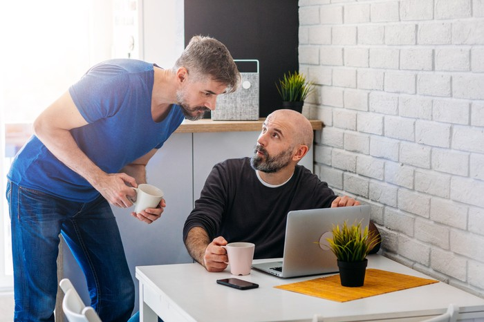 A man sitting at his laptop discusses something with a man standing next to him.