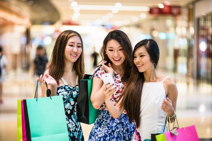 Trois jeunes femmes faisant du shopping à Singapour.