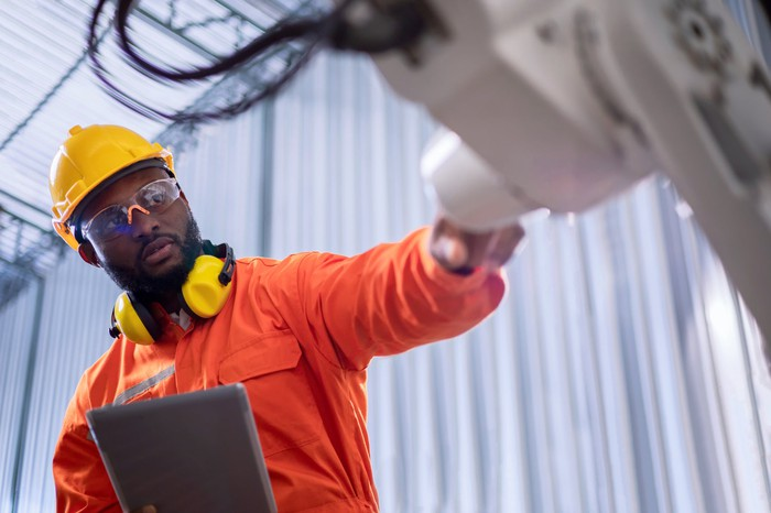 An engineer inspects a robotic arm while working on his tablet.