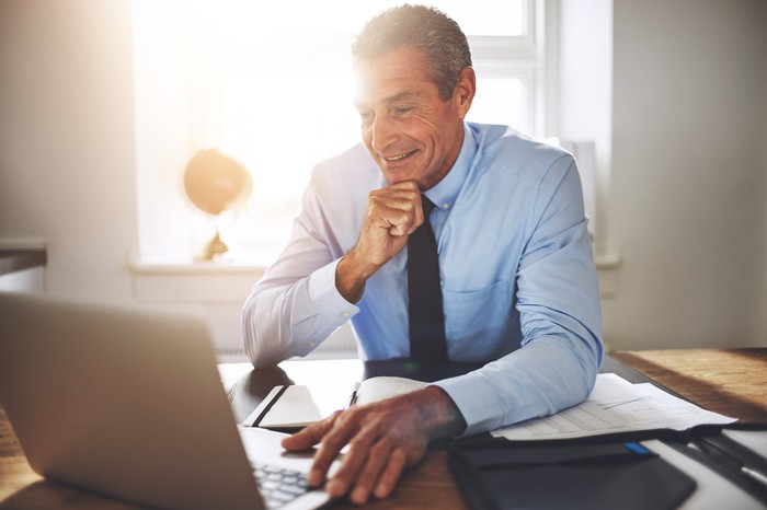 Smiling person resting fingers on laptop
