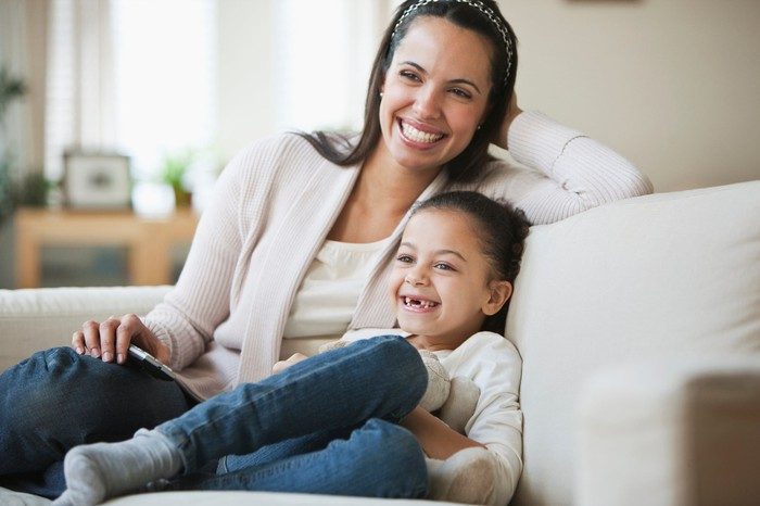 Mother and daughter smiling while sitting on couch