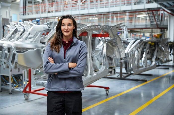 Un ingénieur devant une chaîne de montage automobile.