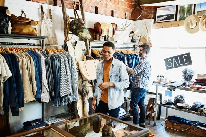 Deux personnes faisant du shopping dans un magasin de vêtements avec des blazers, des chemises et des accessoires.