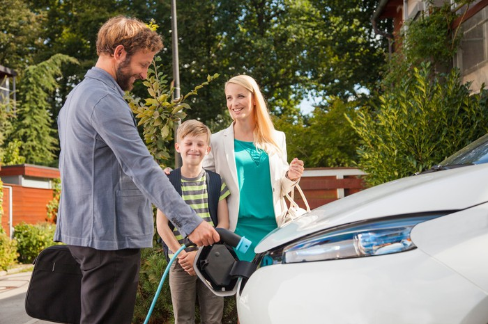 Man charging electric car in domestic garden, woman and boy looking at him and smiling.