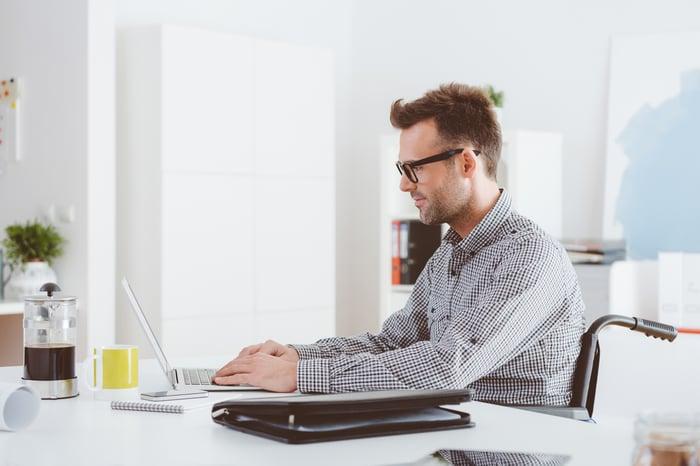 Une personne en fauteuil roulant travaille sur un ordinateur portable.