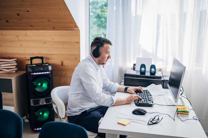 A remote worker wearing a headset and typing on a keyboard at home.