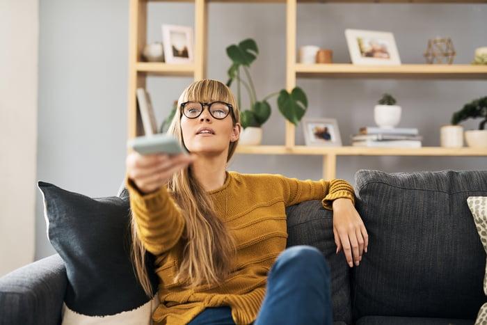Une femme assise sur un canapé et pointant une télécommande de télévision.