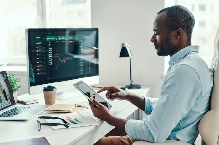 Un homme regardant une tablette assis à un bureau.