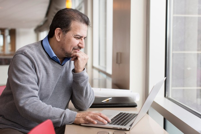 Man squinting while resting hand on laptop