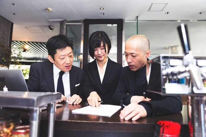 Three people ponder signing a contract on a table in front of them.