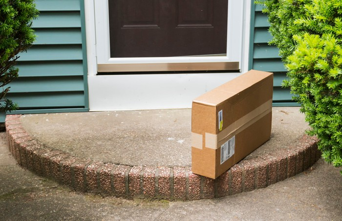 A package sitting on the front doorstep of a house.
