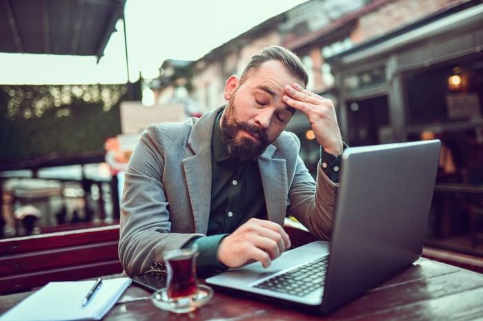 Un investisseur stressé boit du thé dans un café tout en travaillant avec un ordinateur portable.
