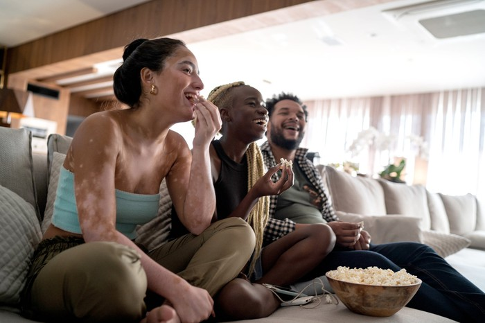 Three people sitting on a couch while sharing a bowl of popcorn and laughing.