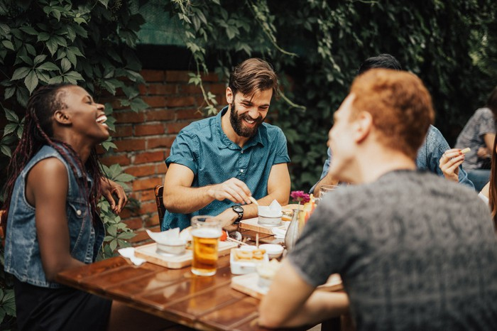 Friends enjoying a meal and laughing.