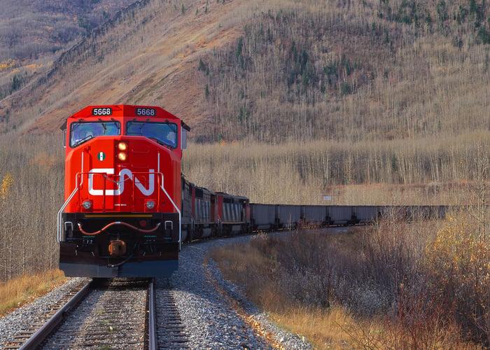A Canadian National train cuts through a mountain pass.