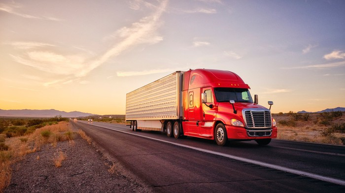 A heavy duty truck hauls cargo down a desert highway.