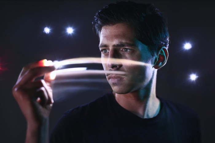 Young entrepreneur  moves his  hands and light streaks emanate from fingers.