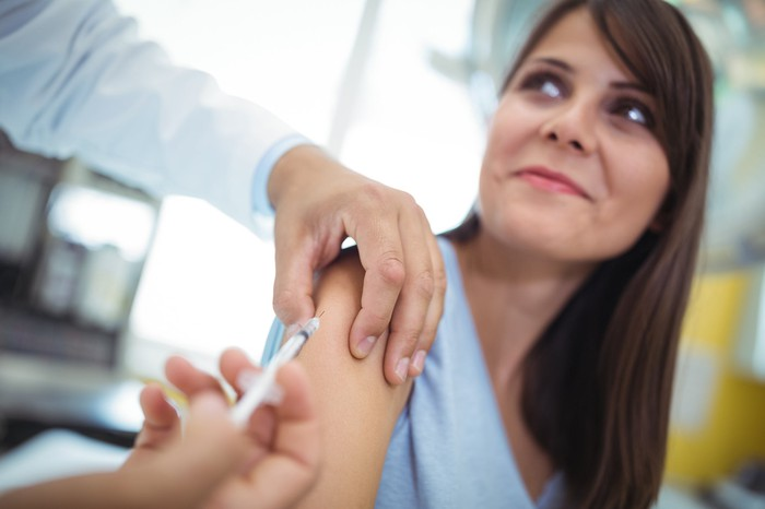 A person administering a vaccine into the right arm of a young woman.