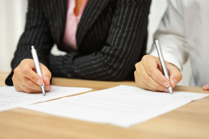 Two people sitting down and signing a document each.