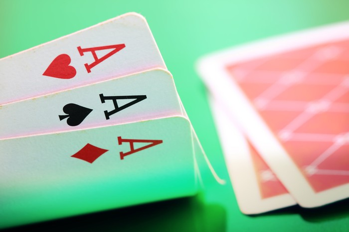Three playing cards are turned up a little revealing three aces.