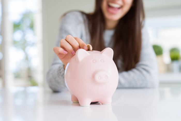 Women putting extra money in her piggy bank
