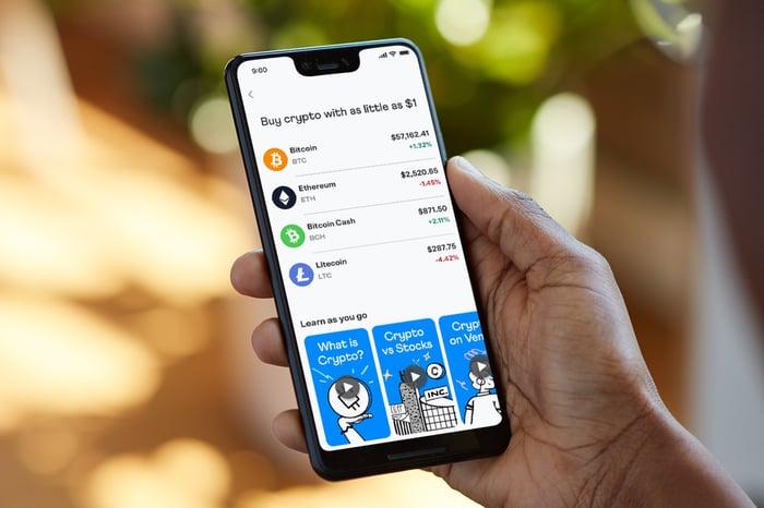 持有智能手机的人,在Venmo应用程序中查看四种不同的加密货币。