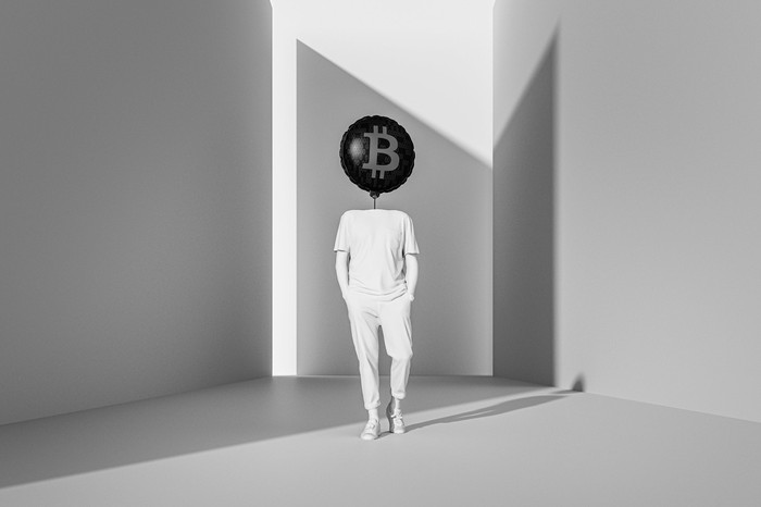 Person walking with their head replaced by a bitcoin balloon