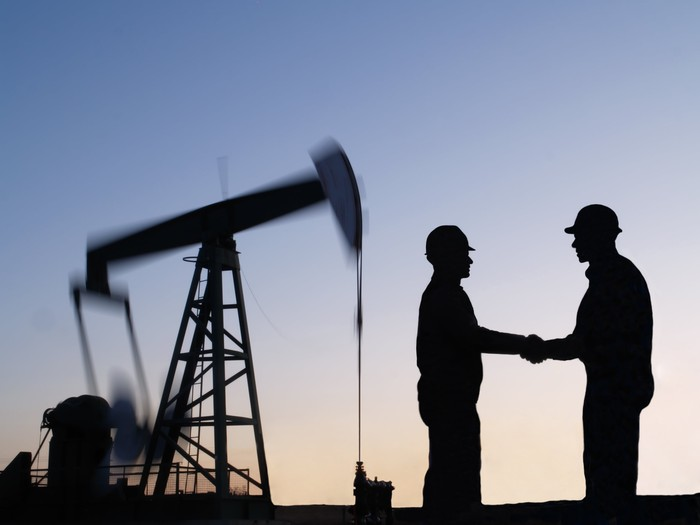 The silhouette of two people shaking hands near an oil pump.