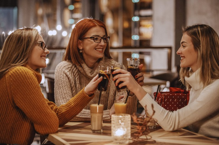 A group of friends clinking glasses of soda together while sitting at a table.