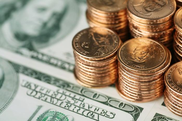 Billets de cent dollars et piles de pièces d'or.