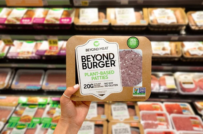 Hand holding package of Beyond Meat's Beyond Burger.