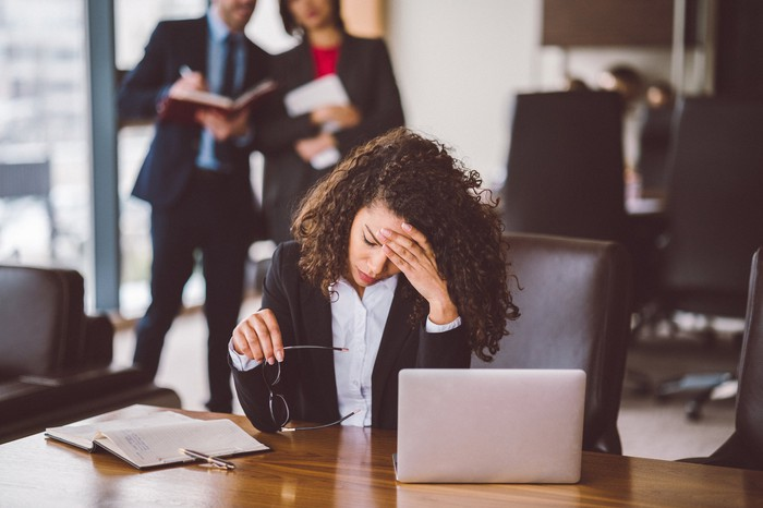 Businessperson in office looking at laptop and holding head.