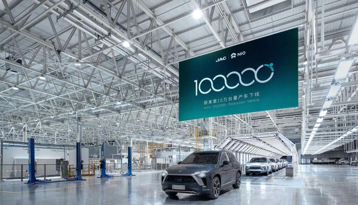 The 100,000th NIO, an ES8 SUV, is shown rolling off a factory production line under a commemorative banner.