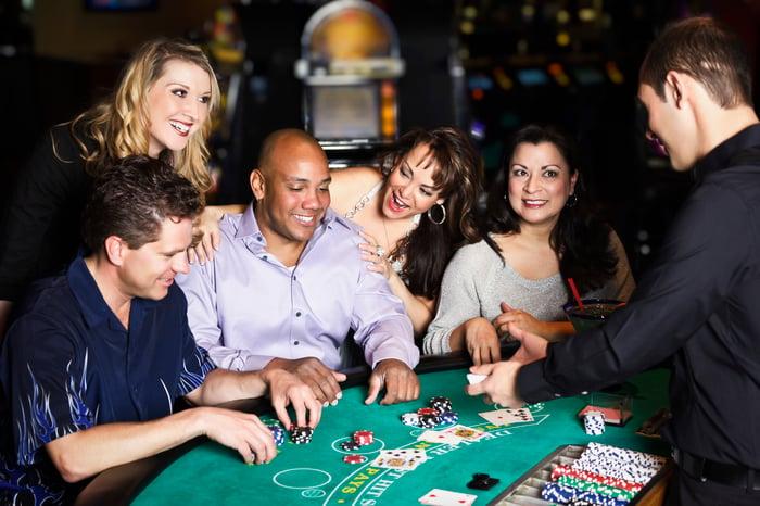 Cinq personnes à une table de casino avec un employé qui distribue des cartes.