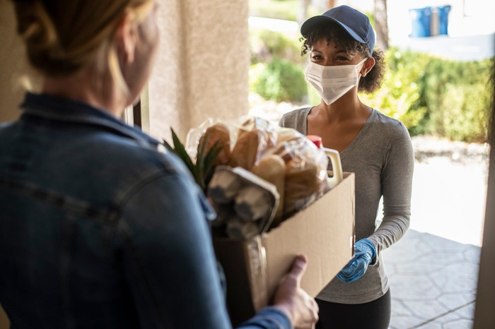 A woman delivering groceries to a customer.
