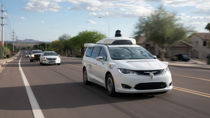 A Wamo vehicle with lidar sensor on top goes down a road with traffic behind it.
