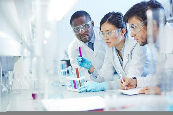 Three lab technicians examining vials and liquid and making notes.