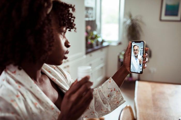 Un jeune discute par vidéo avec un médecin sur un téléphone portable tout en tenant un flacon de pilules devant la caméra.