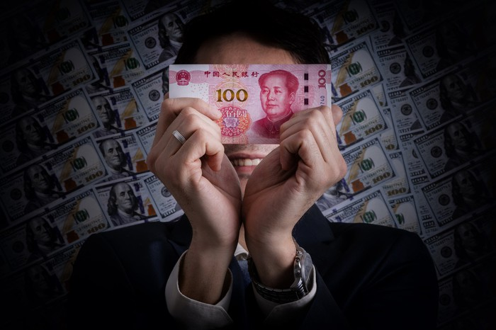 Man in suit holds up 100 yuan note in front of face with $100 bills in the background