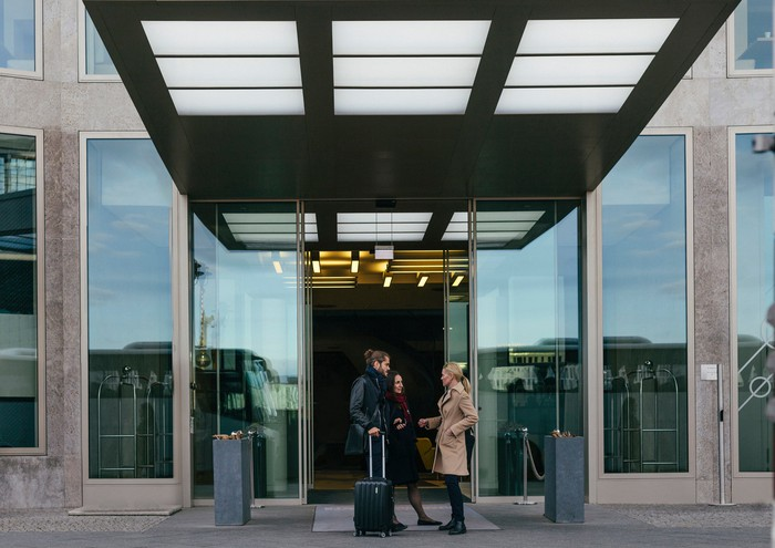Two people with luggage outside the entrance of hotel.